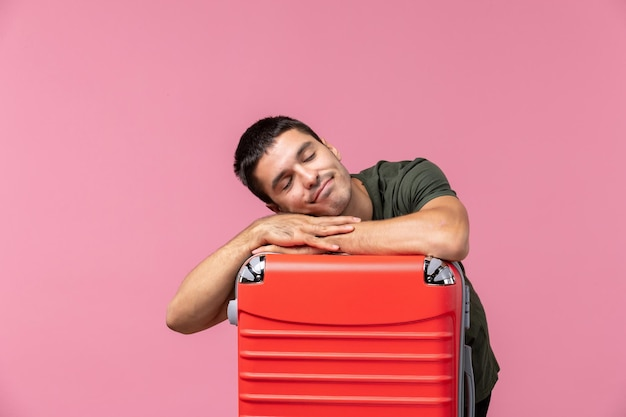 Vorderansicht junger mann, der sich auf die reise vorbereitet und sich auf dem rosafarbenen raum müde fühlt