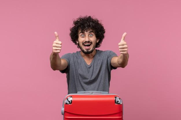 Vorderansicht junger mann, der sich auf die reise vorbereitet und sich auf rosafarbenem raum aufgeregt fühlt