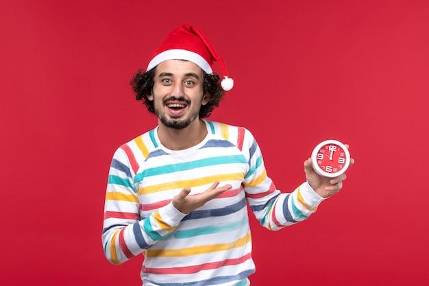 Vorderansicht junger mann, der sich für neue jahre freut, die auf neujahrsferien der roten wandzeit kommen