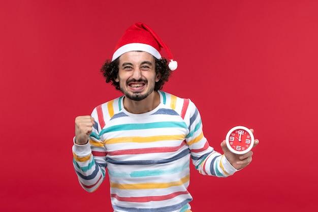 Vorderansicht junger mann, der sich für neue jahre freut, die auf rote wandzeit neujahrsfeiertag kommen