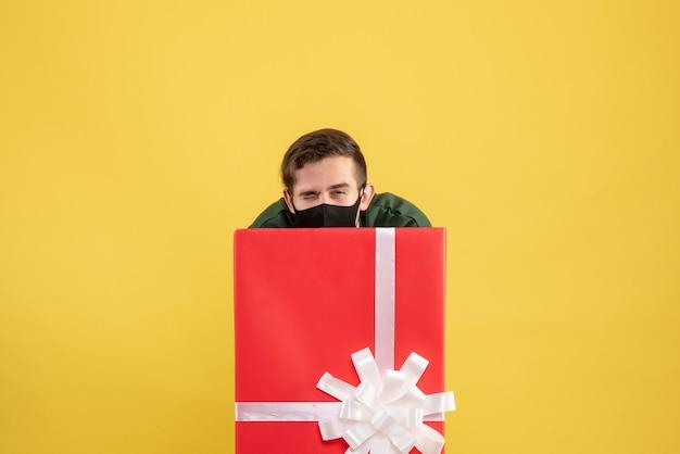 Vorderansicht junger mann, der sich hinter großer geschenkbox auf gelb versteckt