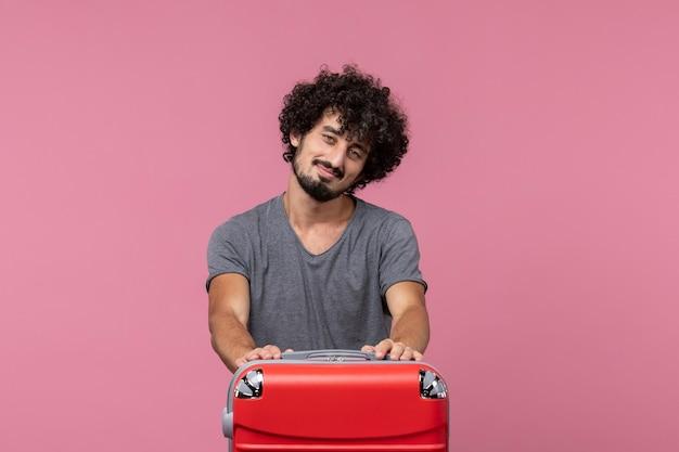 Vorderansicht junger mann, der sich mit seiner roten tasche auf dem rosafarbenen raum auf den urlaub vorbereitet
