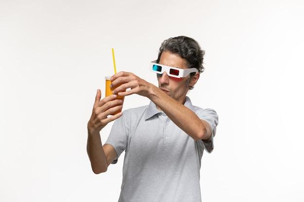 Vorderansicht junger mann, der soda hält und d sonnenbrille auf der einsamen fernbedienung des weißen wandmannfilms trägt