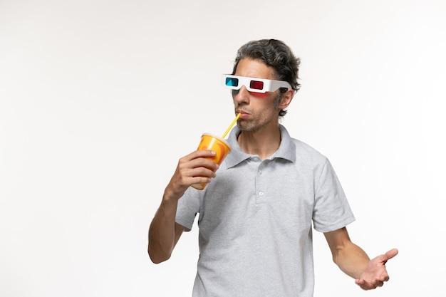 Vorderansicht junger mann, der soda hält und d sonnenbrille auf weißen wandmannfilmen einsame fernbedienung trägt