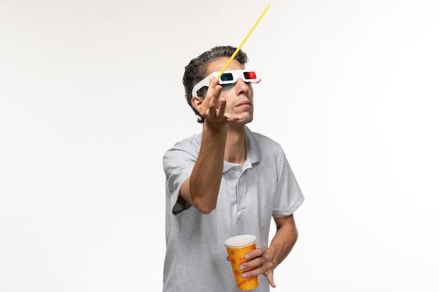 Vorderansicht junger mann, der soda hält und film in d sonnenbrille auf weißem schreibtisch sieht