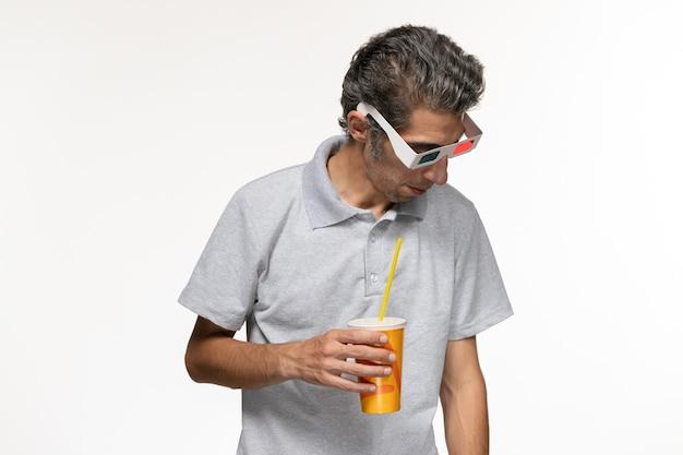 Vorderansicht junger mann, der soda in d sonnenbrille auf weißem schreibtisch ferngesteuertem filmgenuss einsam hält