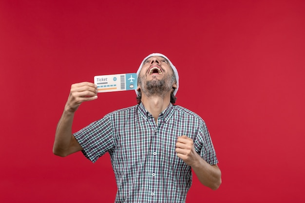Vorderansicht junger mann, der ticket auf rotem hintergrund hält
