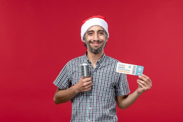 Vorderansicht junger mann, der ticket mit mikrofon auf rotem hintergrund hält