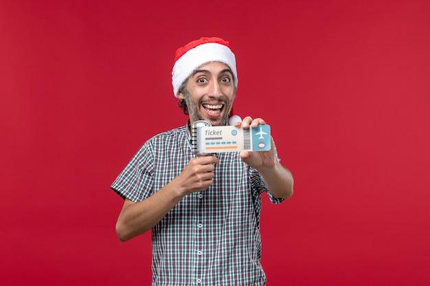 Vorderansicht junger mann, der ticket und mikrofon auf dem roten hintergrund hält