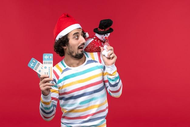 Vorderansicht junger mann, der tickets und spielzeug auf hellrotem wand männlichem rotem feiertags-neujahr hält