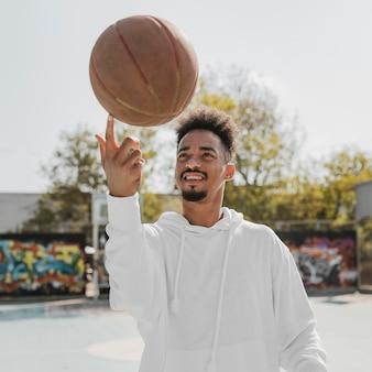 Vorderansicht junger mann, der tricks mit einem basketball tut
