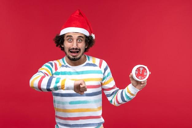 Vorderansicht junger mann, der uhren an den roten neujahrsfeiertagen der roten wand hält