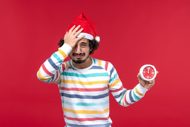 Vorderansicht junger mann, der uhren auf männlichem neujahrsferienrot der roten wand hält