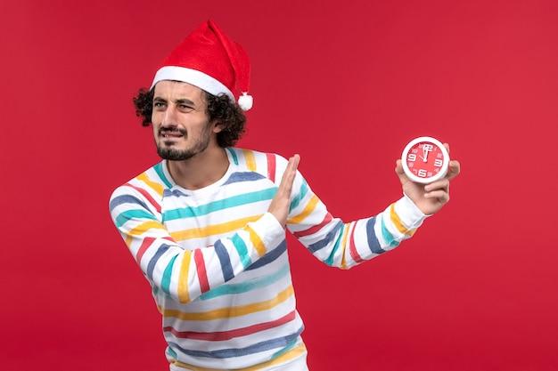 Vorderansicht junger mann, der uhren auf rotem männlichem feiertag der roten wand des neuen jahres hält