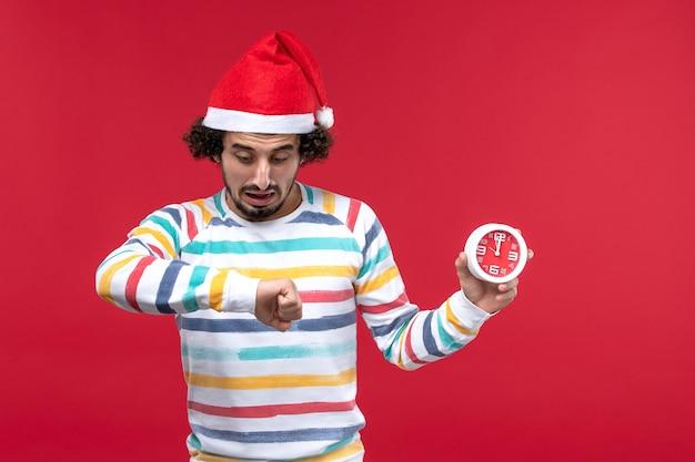 Vorderansicht junger mann, der uhren auf rotem neujahrsfeiertag der roten wand hält