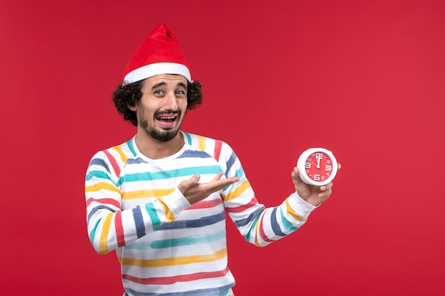 Vorderansicht junger mann, der uhren auf roter wand rotem neujahrsfeiertagsemotionsgefühl hält