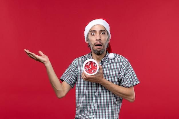 Vorderansicht junger mann, der uhren mit erschrockenem ausdruck auf rotem hintergrund hält