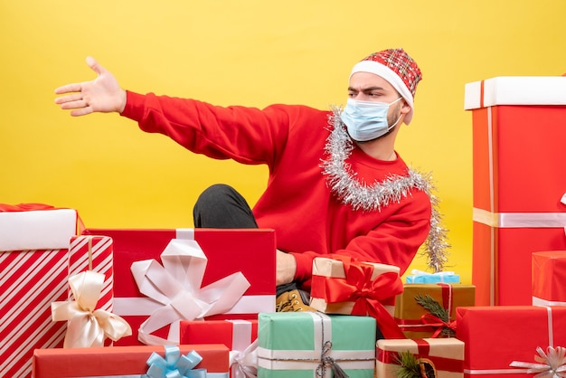 Vorderansicht junger mann, der um geschenke auf gelbem hintergrund sitzt