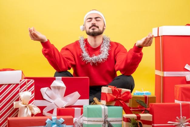Vorderansicht junger mann, der um geschenke sitzt und auf gelbem hintergrund meditiert