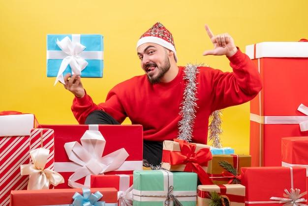 Vorderansicht junger mann, der um geschenke sitzt und eins auf gelbem hintergrund hält