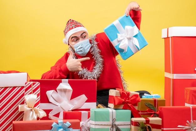 Vorderansicht junger mann, der um weihnachtsgeschenke auf gelb sitzt