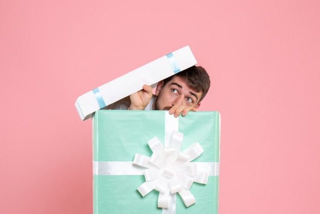 Vorderansicht junger mann, der versucht, sich in der gegenwärtigen box auf rosa menschlichem farbschlaf-schlaf-pyjama-party-menschenspiel zu verstecken