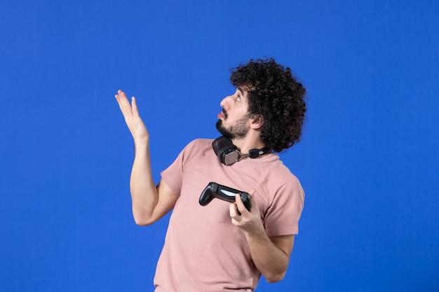 Vorderansicht junger mann, der videospiel mit schwarzem gamepad auf blauem hintergrund spielt virtuelles jugendlich jugendsofa erwachsene freude fußballspieler gewinnen