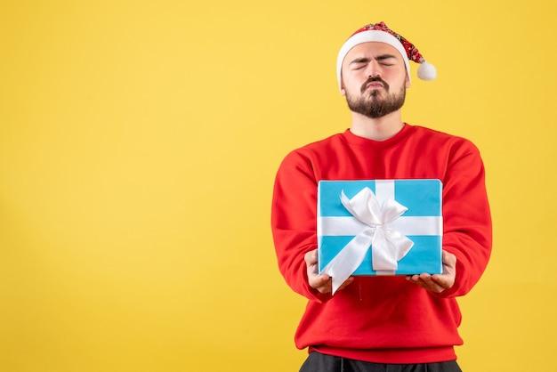 Vorderansicht junger mann, der weihnachten auf gelbem hintergrund hält