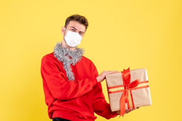 Vorderansicht junger mann, der weihnachten in steriler maske hält