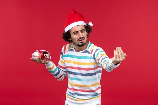 Vorderansicht junger mann, der weihnachtsbaumspielzeug auf rotem menschlichem neujahr des feiertags der roten wand hält