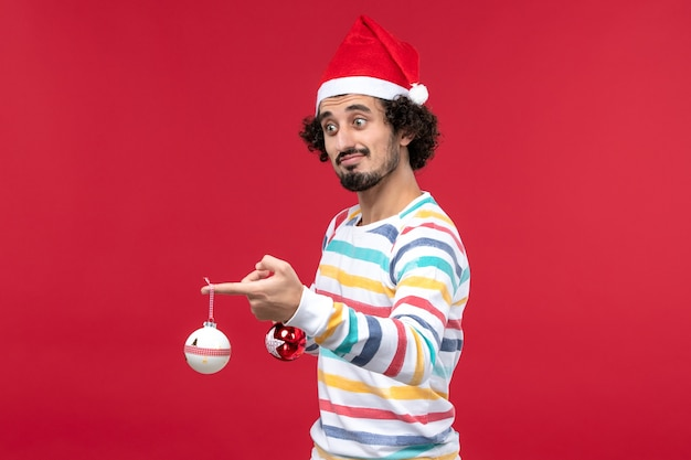 Vorderansicht junger mann, der weihnachtsbaumspielzeug auf rotem neujahrsfeiertagsmensch der roten wand hält