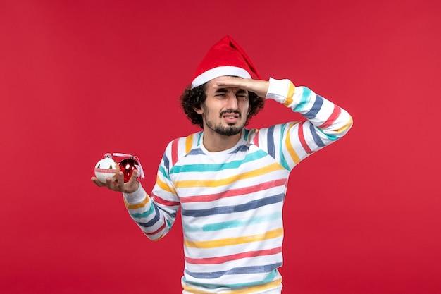 Vorderansicht junger mann, der weihnachtsbaumspielzeug auf rotem wandfeiertag roten menschen neues jahr hält