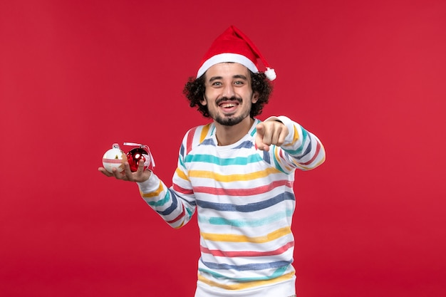 Vorderansicht junger mann, der weihnachtsbaumspielzeug auf rotem wandfeiertag roter mensch hält
