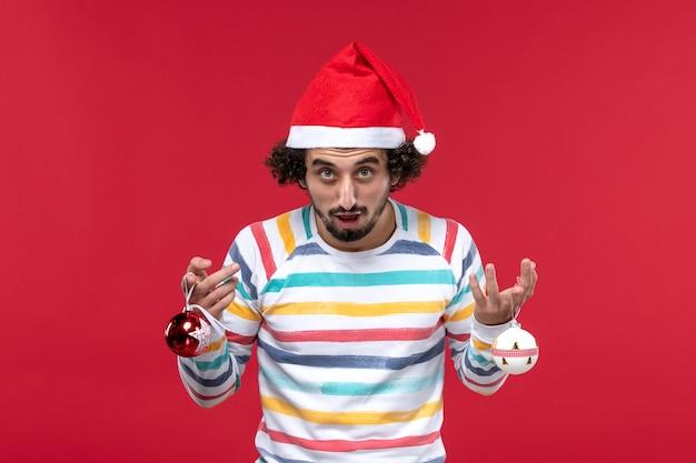 Vorderansicht junger mann, der weihnachtsbaumspielzeug auf rotem wandrotmodell-neujahrsfeiertag hält