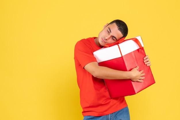 Vorderansicht junger mann, der weihnachtsgeschenk auf gelbem hintergrund umarmt