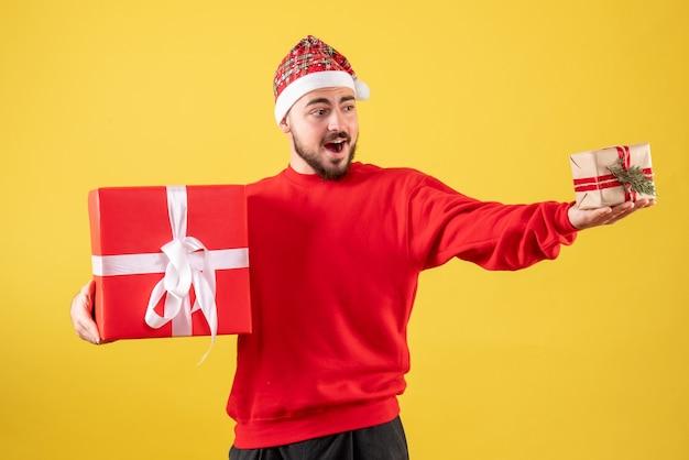 Vorderansicht junger mann, der weihnachtsgeschenke auf einem gelben hintergrund hält