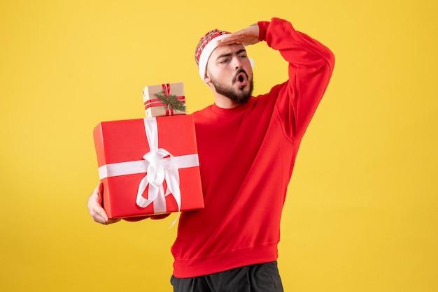 Vorderansicht junger mann, der weihnachtsgeschenke auf gelb hält