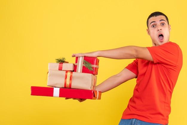 Vorderansicht junger mann, der weihnachtsgeschenke auf gelbem hintergrund hält
