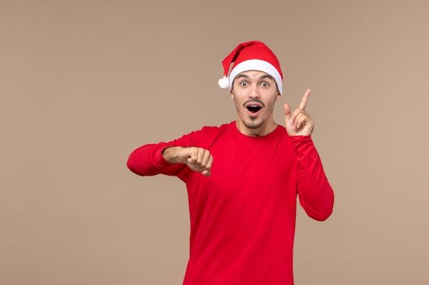 Vorderansicht junger mann, der zeit auf braunem hintergrund emotionen weihnachtsferien prüft