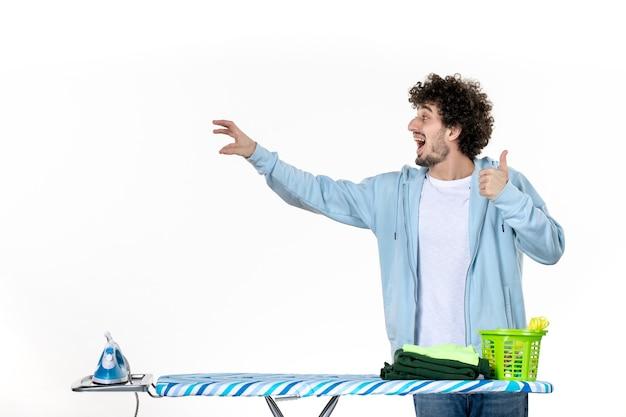 Vorderansicht junger mann hinter bügelbrett auf weißem hintergrund farbe mann reinigung hausarbeit wäsche foto kleidung