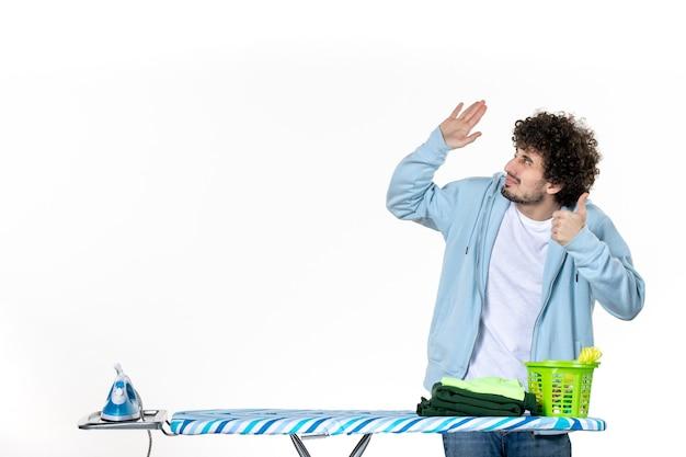 Vorderansicht junger mann hinter bügelbrett auf weißem hintergrund farbe mann reinigung hausarbeit wäsche fotos bügeleisen kleidung