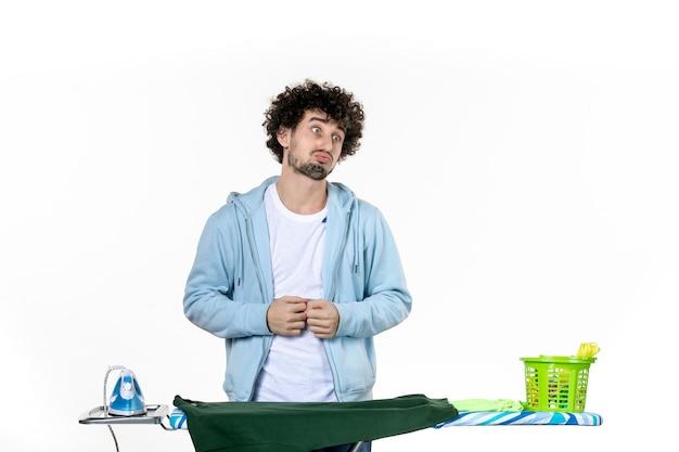 Vorderansicht junger mann hinter bügelbrett auf weißem hintergrund hausarbeit bügeln farben wäsche kleidung reinigung emotion mann