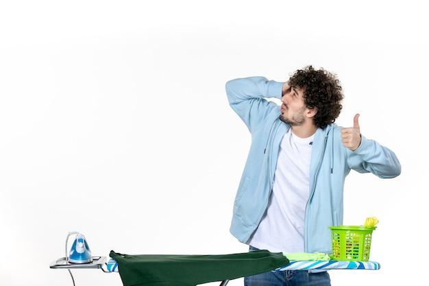 Vorderansicht junger mann hinter bügelbrett auf weißem hintergrund hausarbeit bügeln wäsche kleidung emotion mann farbe