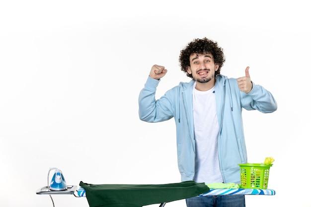 Vorderansicht junger mann hinter bügelbrett auf weißem hintergrund hausarbeit bügeln wäsche kleidung reinigung emotion mann farben
