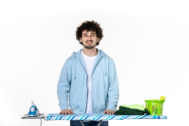 Vorderansicht junger mann hinter bügelbrett auf weißem hintergrund hausarbeit wäsche farbe reinigung kleidung foto bügeleisen