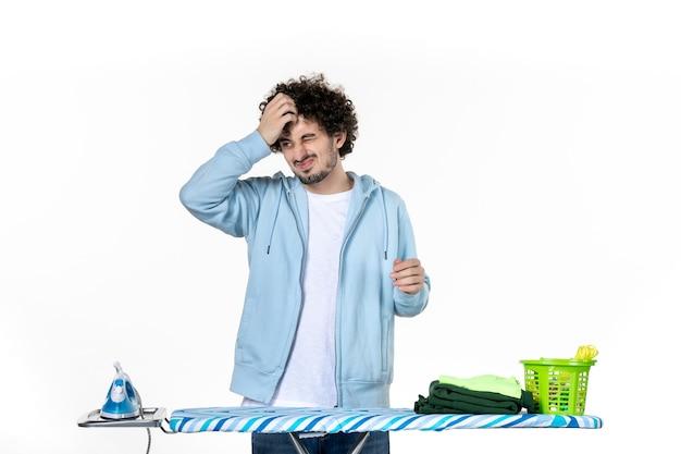 Vorderansicht junger mann hinter bügelbrett auf weißem hintergrund hausarbeit wäschereinigung kleidung fotobügeleisen