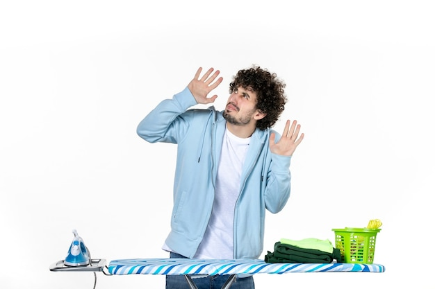 Vorderansicht junger mann hinter bügelbrett auf weißem hintergrund kleidung mann reinigung bügeleisen hausarbeit farbe wäsche foto