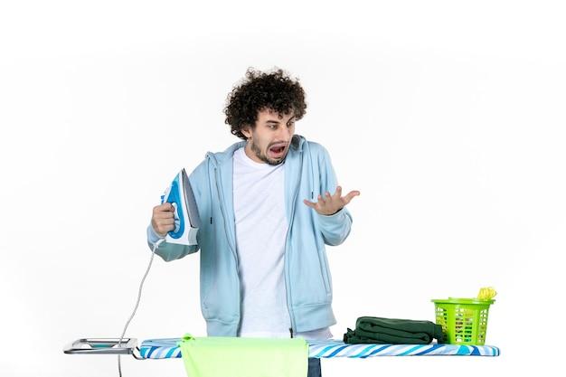 Vorderansicht junger mann hinter bügelbrett hält bügeleisen und verbrennt seine hand auf weißem hintergrund eisenfarbe mann reinigung hausarbeit wäsche foto kleidung