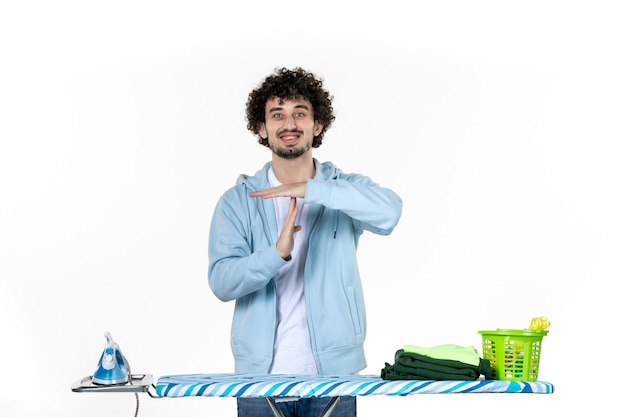 Vorderansicht junger mann hinter bügelbrett machen t zeichen auf weißem hintergrund kleidung mann wäsche foto reinigung bügeleisen hausarbeit farbe