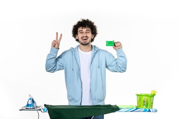 Vorderansicht junger mann hinter bügelbrett mit bankkarte auf weißem hintergrund wäsche hausarbeit farbe menschliches bügeleisen reinigung geld emotion